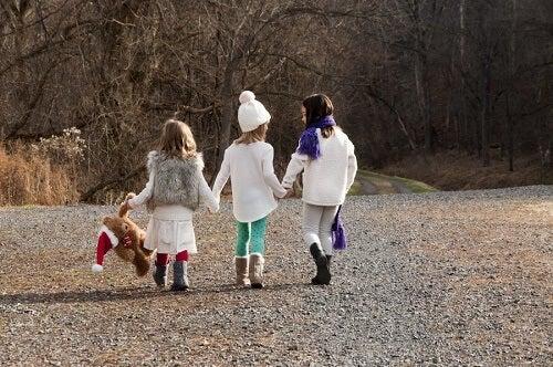Bambine per mano in un parco