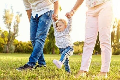 Bambina cammina tenuta dai genitori