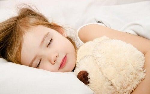 Bimba dorme con peluche