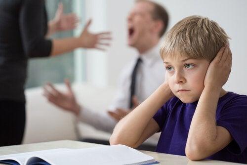 Bambino con mani sulle orecchie per non sentire i genitori che discutono