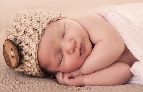 Bebè con cappellino dorme