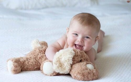 Neonato sorridente con peluche