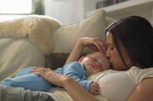 Mamma con bimbo in braccio sul divano
