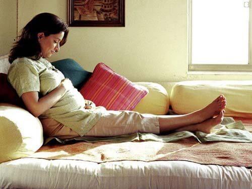 Donna incinta riposa sul divano