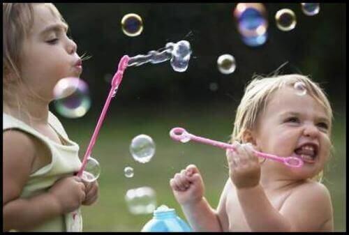 Bimbe giocano con bolle di sapone