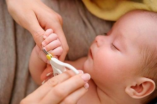 Mamma taglia le unghie a neonato