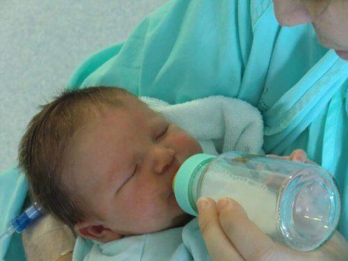 Neonato prende il latte con il biberon