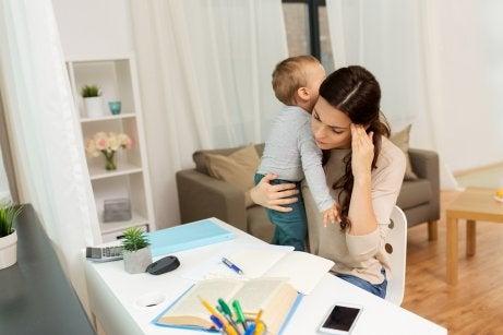 Mamma studia con bambino in braccio