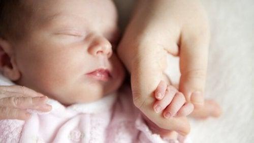 neonato tiene la mano della mamma