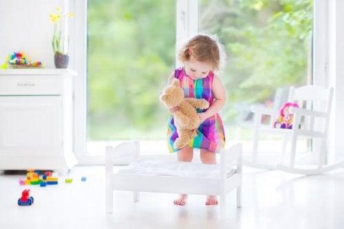 Bambina mette a letto l'orsacchiotto