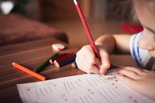 Bambino che scrive seduto a un tavolo.