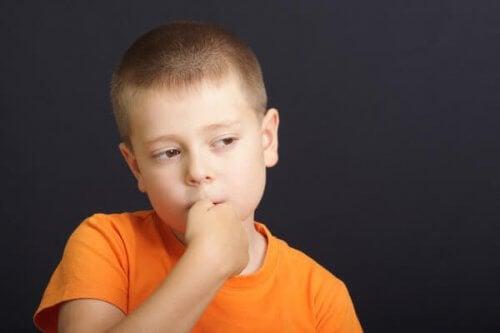 Bambino con le mani in bocca come evitare che i figli si mangino le unghie