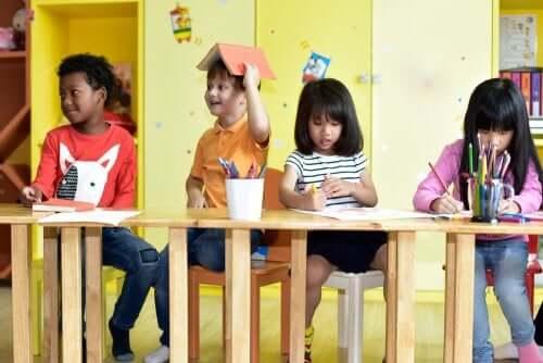 bambini seduti sui banchi disegnano con i colori