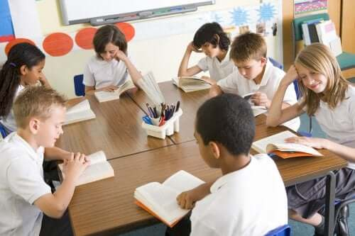 bambini seduti in classe che leggono