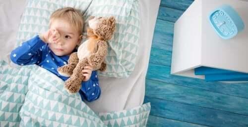 Bambino a letto con peluche