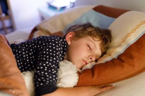 bambino che dorme a letto con orsetto