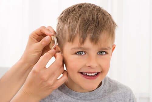 bambino sordo con apparecchio acustico