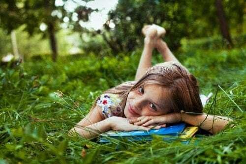 Bambina legge sull'erba e stimola l'apprendimento durante le vacanze