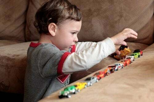 Bambino con autismo gioca con le macchinine