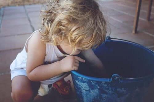 Bambino mancino con un secchio blu