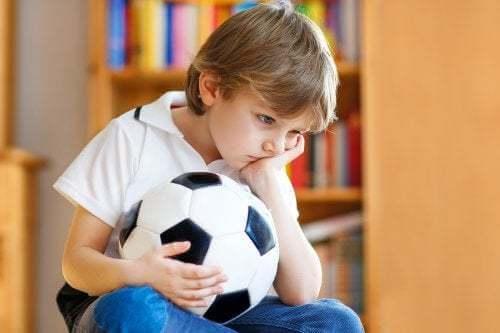 Bambino infelice con un pallone in mano