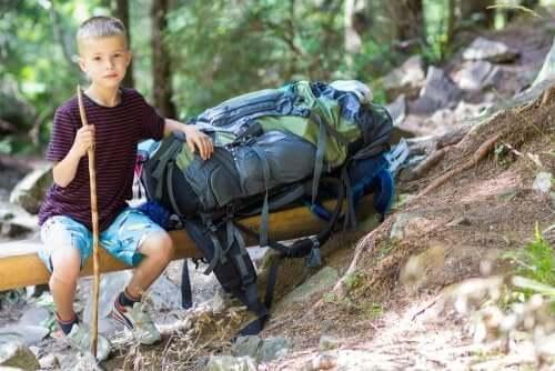 Bambino seduto in un bosco