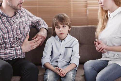 Genitori che discutono davanti al figlio annoiato