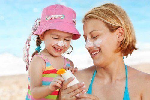 Mamma e figlia mettono la crema solare