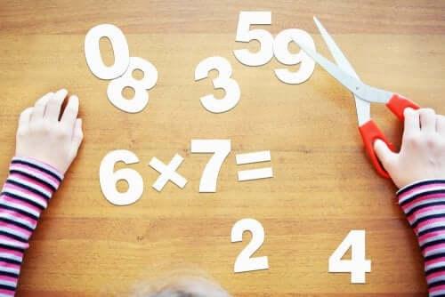 Bambino che ritaglia numeri di carta
