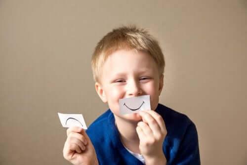 Bambino con fogliettini con emoticon felice e triste