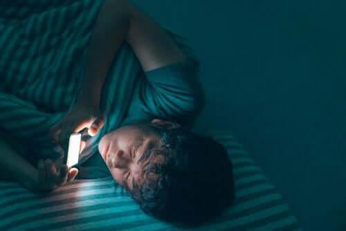 Adolescente che usa il cellulare di notte