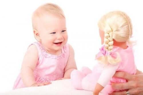 Bambina che ride guardando una bambola