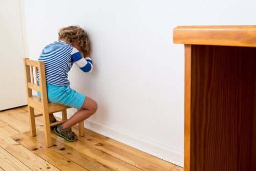 bambino seduto faccia al muro per castigo