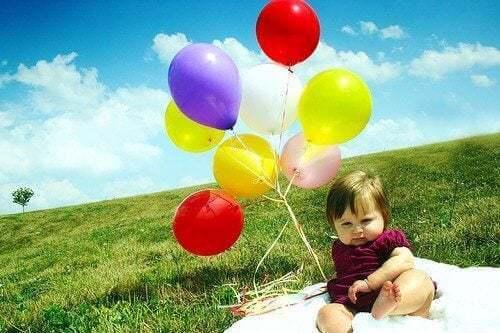 Bambino con palloncini colorati su un prato