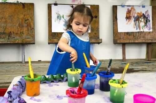 bambina che gioca con i colori e dipinge dei quadri