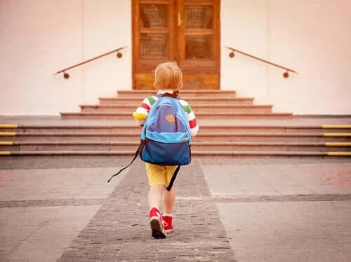 Bambino che entra a scuola.