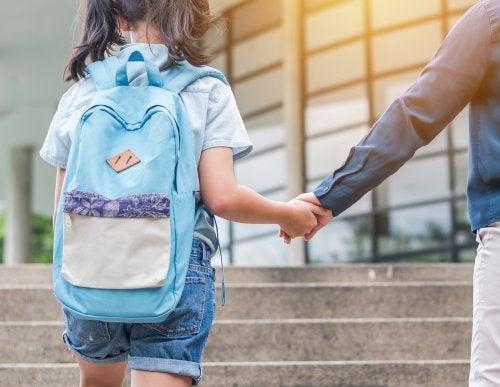 Genitore che accompagna la figlia a scuola.