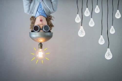 Il metodo Design Thinking è una metodologia che consente di trovare soluzioni nuove. Bambino a testa in giù con lampadina in testa.