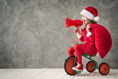 Frasi natalizie per i più piccoli: bambina sul triciclo vestita da babbo natale.