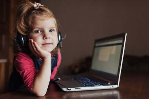 La teoria dell'esperienza dell'apprendimento bambina che studia al computer con delle cuffie.