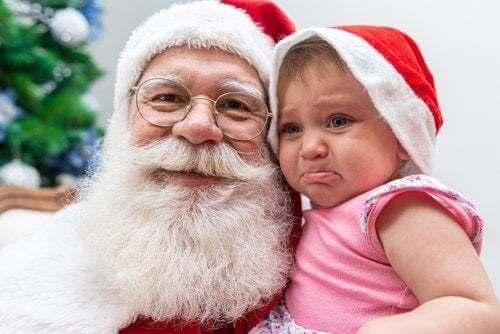Bambina piange in braccio a Babbo Natale.