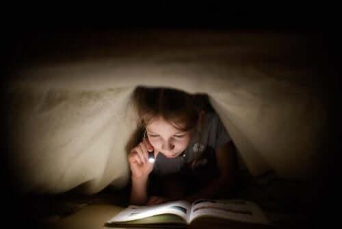 Bambina che legge sotto le coperte con la torcia