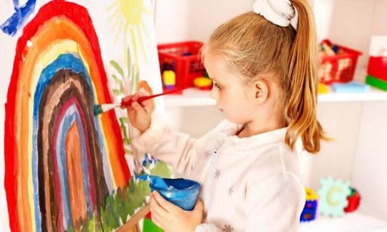 Bambina pittura con tempere e pennello