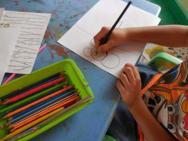 Bambino che disegna e matite colorate