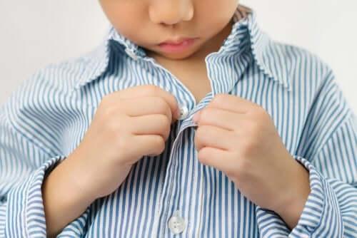 bambino che si abbottona la camicia da solo