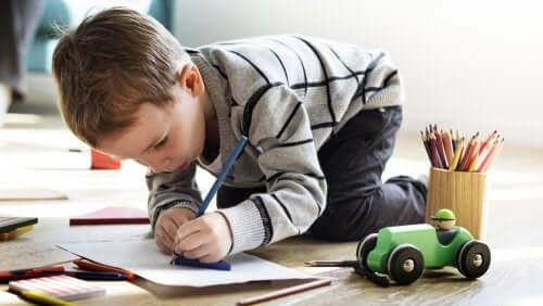 Bambino che disegna su un foglio con una matita