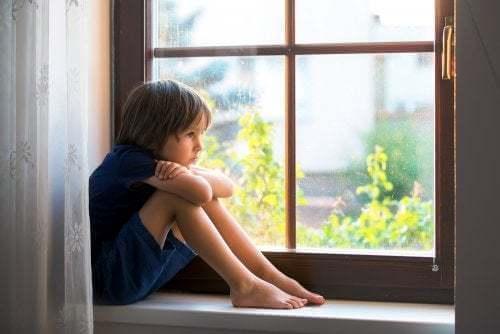 Bambino triste guarda fuori dalla finestra.