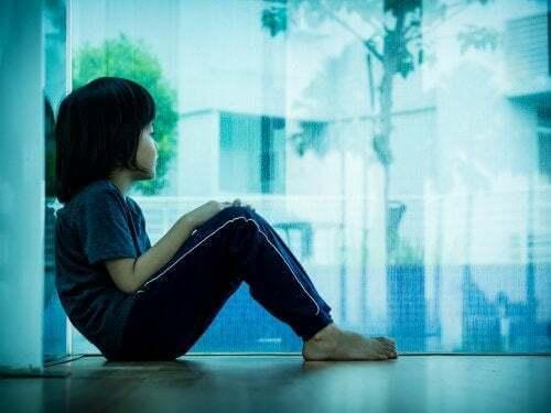 Bambino triste alla finestra.