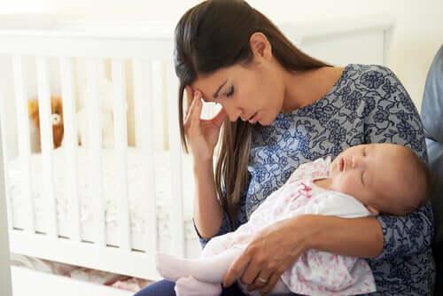 Mamma depressa con figlio neonato in braccio.