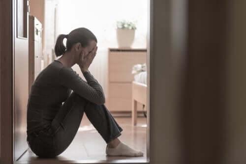 Donna seduta sul pavimento con depressione post partum.